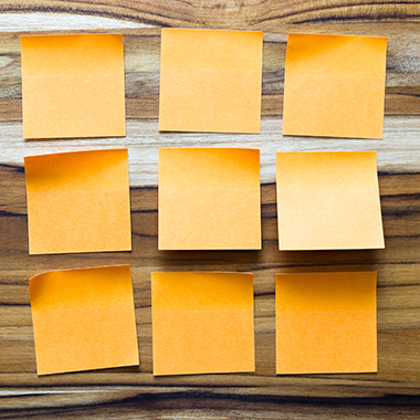 Arrangement of orange sticky notes on wood background
