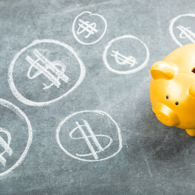 Piggy bank and money on chalkboard