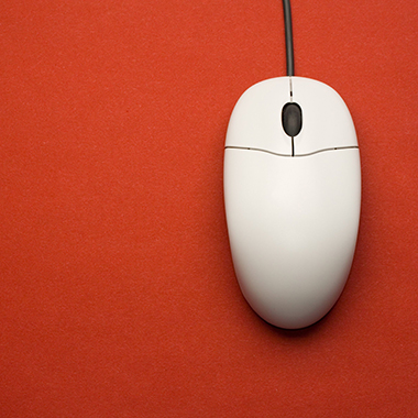 Overhead view of white mouse on red background