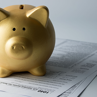 Golden piggy bank on income tax form
