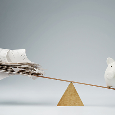 Piggy Bank Balancing on Seesaw Over Bills
