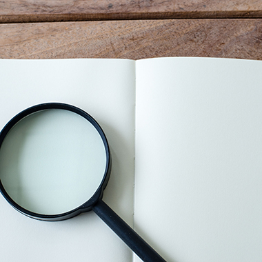 Magnifying Glass on White Open Notebook