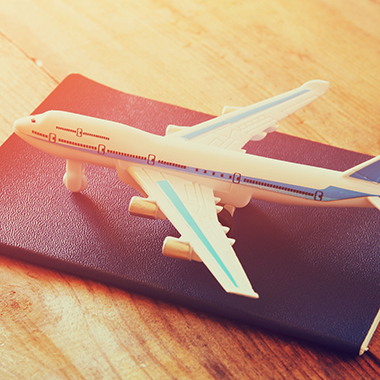 Toy Airplane & Passport on Wooden Table