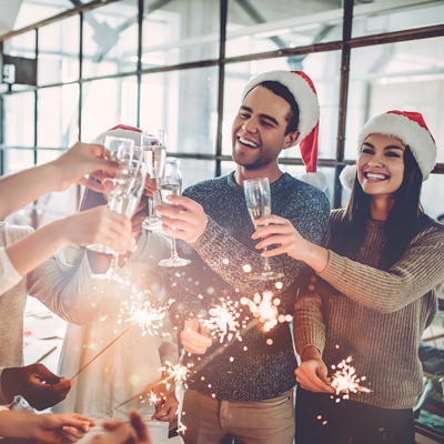 Coworkers clinking champagne glasses at office holiday party